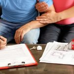 Young Couple Signing Loan Contract. Concept: cross collateralization