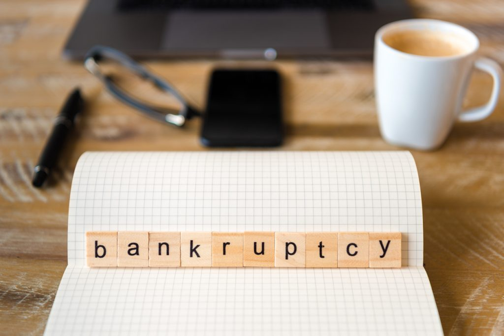 Closeup on notebook over wood table background, focus on wooden blocks with letters making Bankruptcy word. Business concept image. Laptop, glasses, pen and mobile phone in a defocused background. Concept: rebuild credit