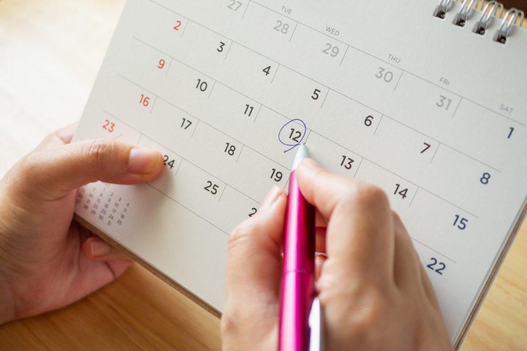 Mano de mujer señalando fecha en un calendario. Concepto: ¿Qué es un préstamo a plazos?