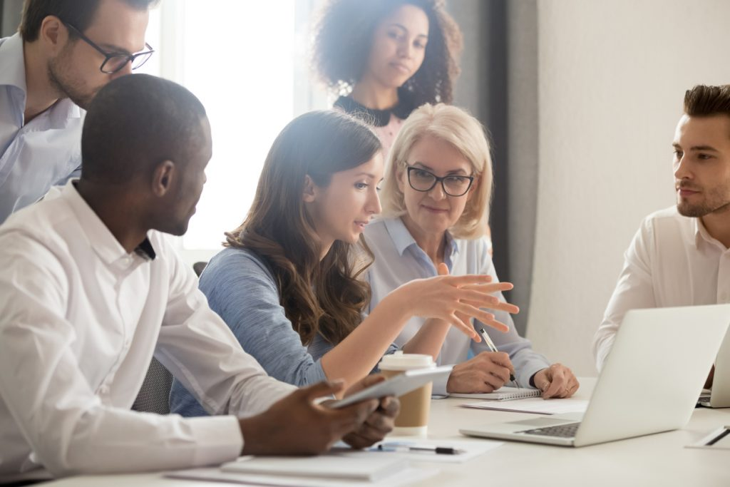 Joven consultora profesional entrenando a empleados en oficina. Concepto: ¿Cómo comenzar un negocio de consultoría?
