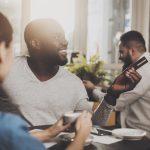 Joven afroamericano en un restaurante pagando con tarjeta de crédito con reembolsos