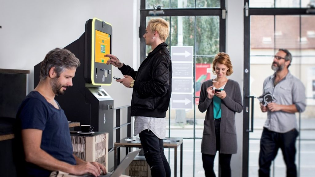 People stand at BITCOIN ATM and buy the cryptocurrencies. Concept: How to choose a bank