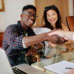 Pareja de dueños de negocio estrechando mano a inversor. Concepto: Cómo coseguir a inversores para tu negocio