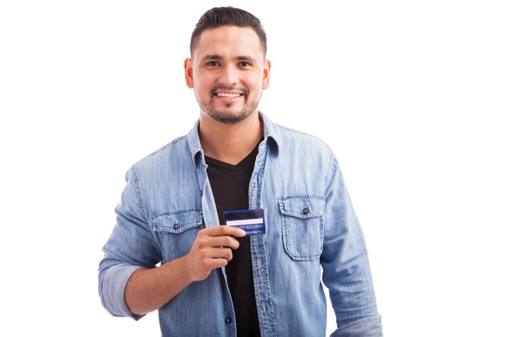 Portrait of a Hispanic young man dressed casually and holding his favorite credit card against a white background. Concept: Best Credit Cards to Build Credit