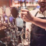 foto de un bartender alegre sirviendo bebidas y sonriendo. Concept: cómo abrir un bar