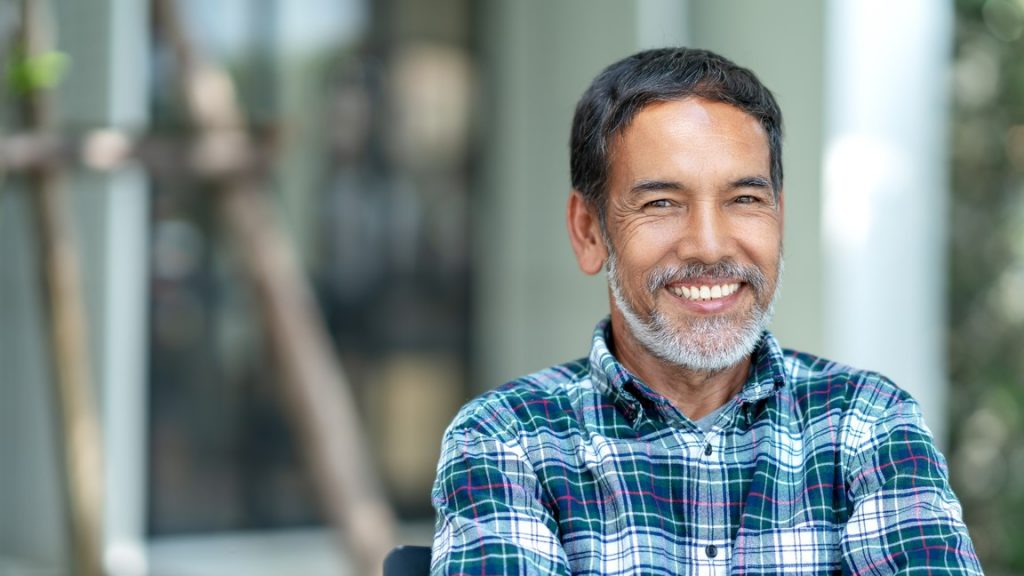Portrait of happy mature man with white, grey stylish short beard looking at camera outdoor. Casual lifestyle of retired hispanic people or adult asian man smile with confident at coffee shop cafe. Concept: how to open a bar