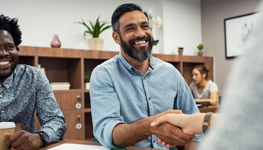 Two business people shaking hands while sitting in meeting room. Middle eastern businessman shake hands to businesswoman. Portrait of happy smiling latin man signing off deal with an handshake. Concept: debt settlement