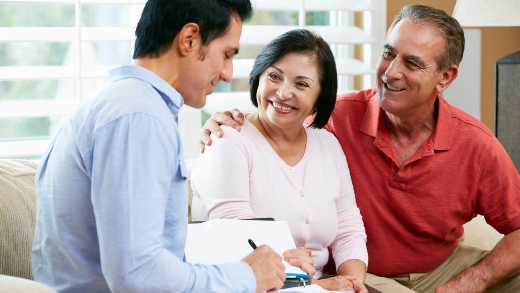 Financial Advisor Talking To Senior Couple At Home Writing Documents Smiling. cconcept: What is a down payment?
