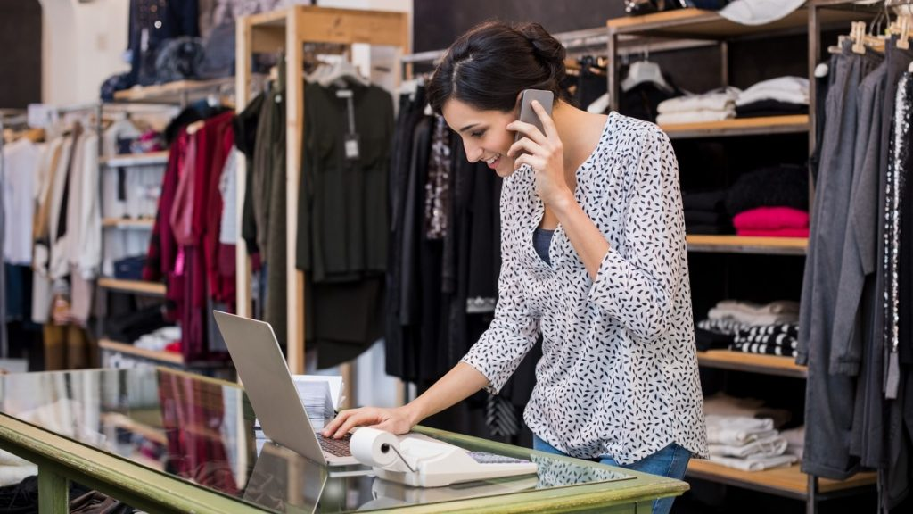 Young businesswoman talking over phone while checking laptop in her clothing store. Young entrepreneur in casual using laptop and talking on mobile. Store manager woman checking important documents on laptop. Small business concept. concept: What is a down payment?