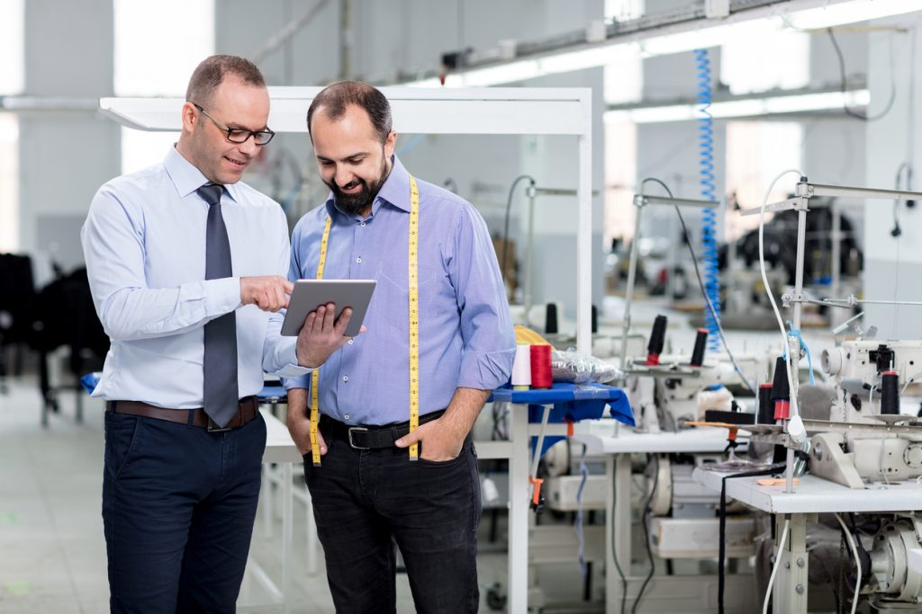 Financial advisor and small business owner work with tablet in textile factory.Concept: What is the true cost to own a business?