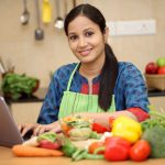 Home-based chef using a tablet computer in her kitchen and starting a food business from home