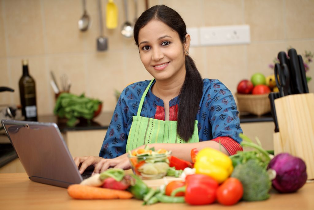 Cocinera en casa con computadora, montando un negocio de comida desde casa.