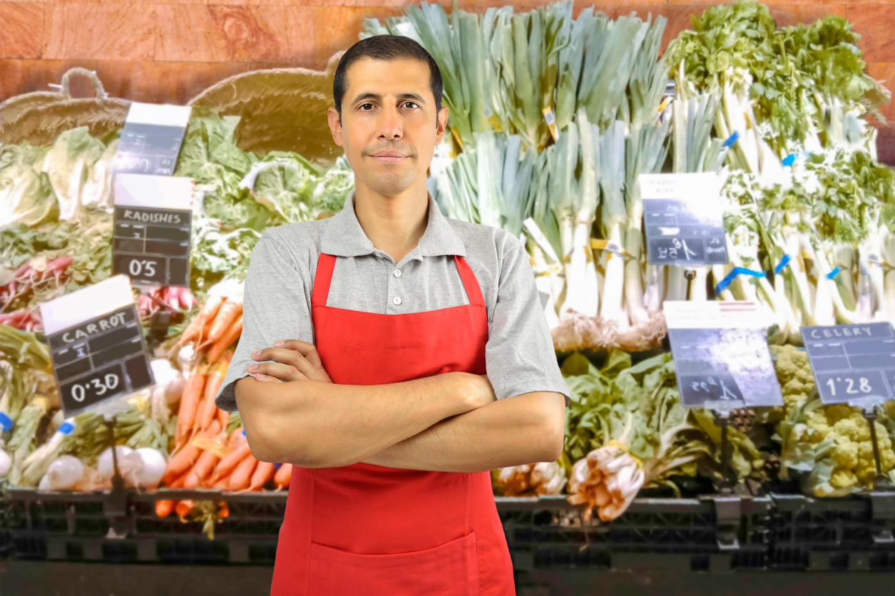 portrait of shopman at the vegetables store with crossing arms. Concept: FICA withholding