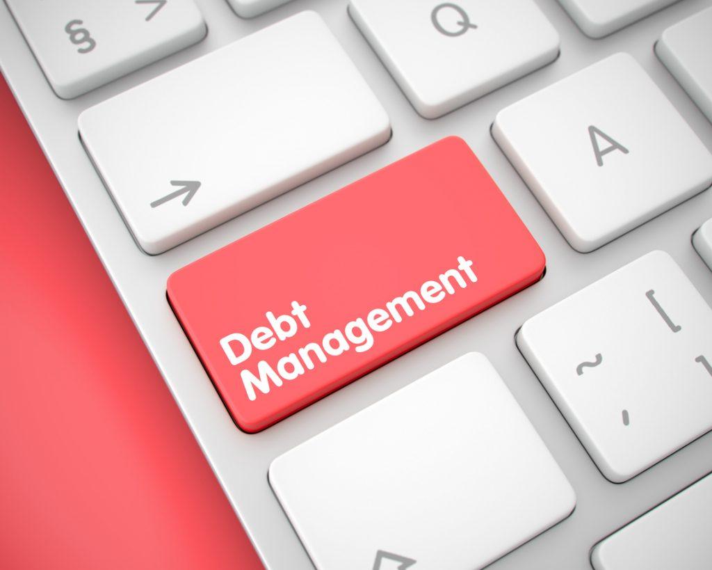 Close up de un teclado blanco con una tecla roja de programa de administración de deudas. Concept: programa de administración de deudas