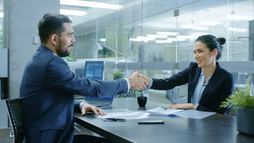 Businesswoman and Businessman Shake Hands. Draw up a Contract, Filling Papers in Conference Room. In the Background Modern Bright Office with Glass Walls. Concept: Debt Management Program