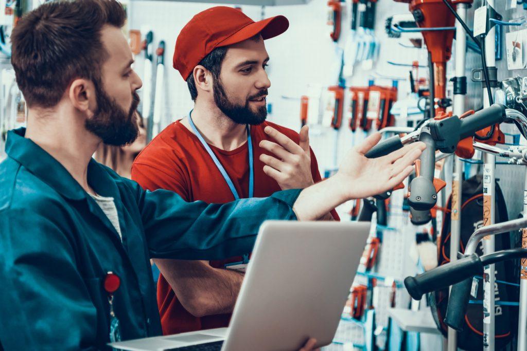 Dependiente y cliente comprando herramientas en tienda especializada. Concepto: Gastos variables.