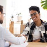 Cliente en banco con prestamista acordando un préstamo y una tarifa de originación.