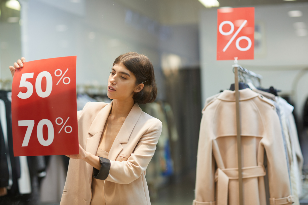 Waist up portrait of beautiful woman hanging red SALE signs on window display in clothes store, copy space. Concept: black friday tips