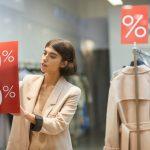Retrato de una mujer colgando un letrero rojo de descuentos en su tienda de ropa. Concept: Consejos para black friday