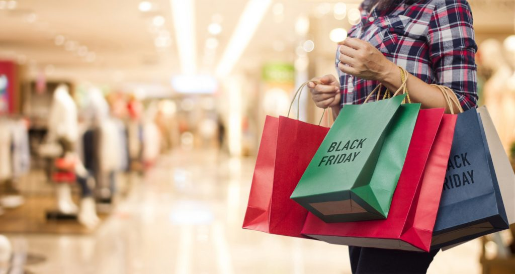 Black Friday, Woman holding many shopping bags while walking in the shopping mall background. Concept: black friday tips