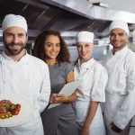 Portrait of restaurant manager with his kitchen staff in the commercial kitchen. Concept: most popular types of restaurants