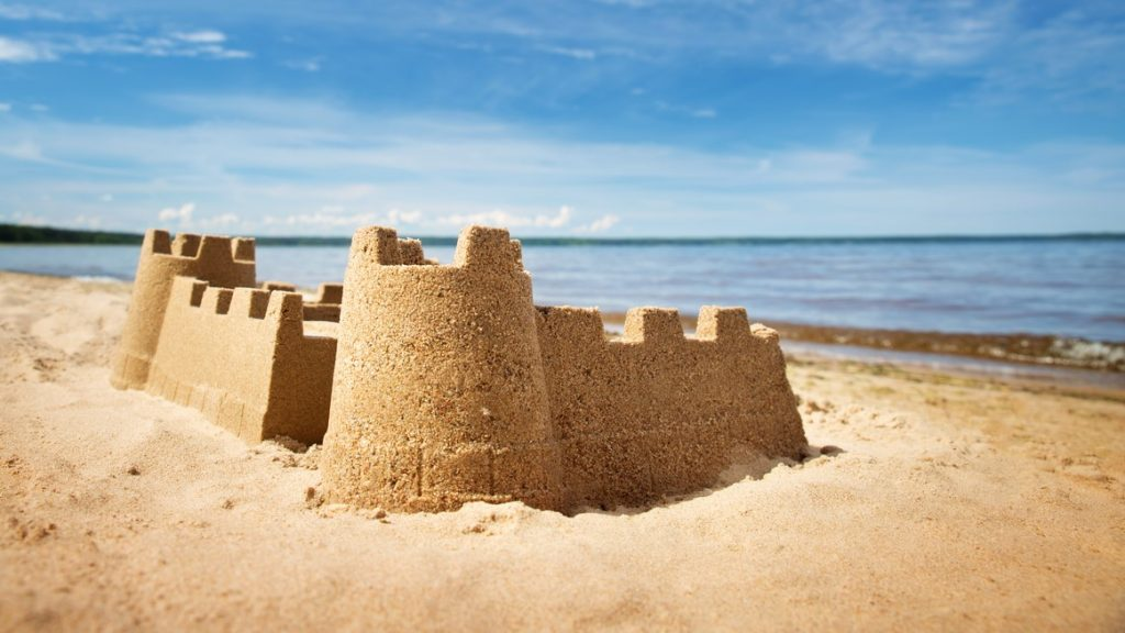 Sandcastle on the sea in summertime. Seashore on beautiful day. Sand on the beach and blue water. concept: Credit Utilization