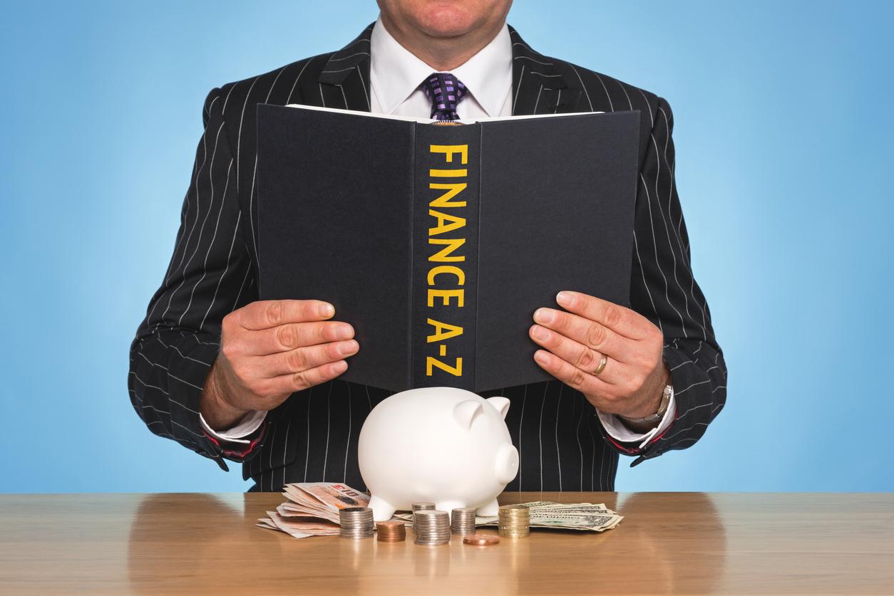 A businessman sat at a desk reading a FINANCE A-Z book. Concept: financial terms