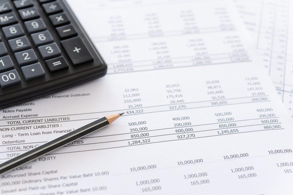 Primer plano de extractos bancarios sobre escritorio junto con calculadora y pluma.