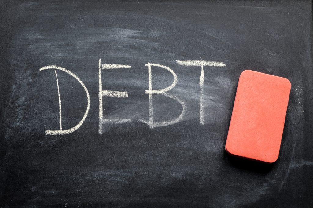 Eliminar deuda, palabra escrita con tiza en pizarron siendo borrada. concept: administración de la deuda