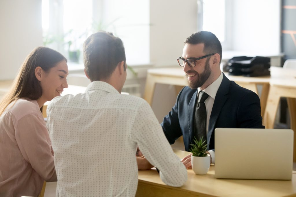 Friendly lawyer or financial advisor in suit consulting young couple, smiling investment broker or bank worker making loan offer, giving legal advice, selling insurance or real estate to customers. Concept: Debt Management Tips