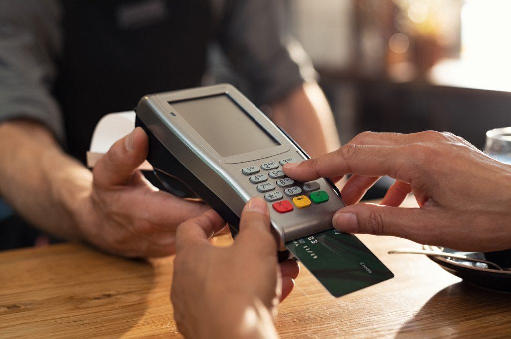 Closeup de una mano usando una terminal de pago con tarjeta. Concept: utilización de crédito