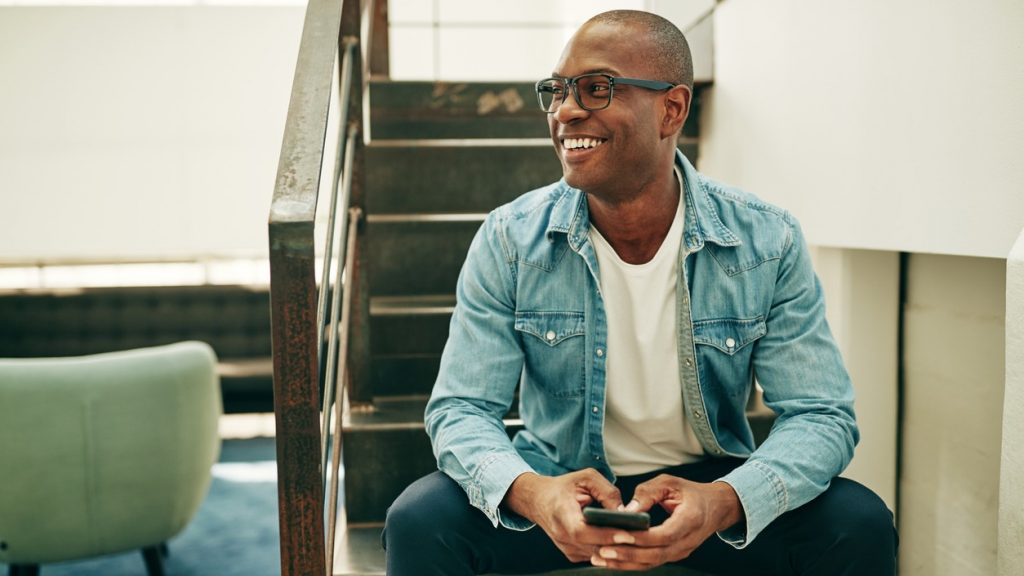 Smiling young African businessman wearing glasses and reading text messages on a cellphone while sitting on stairs in an office. Concept: credit utilization