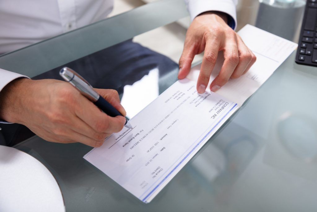 Businessman's Hand Signing Cheque On Glass Desk. Concept: How to write a check