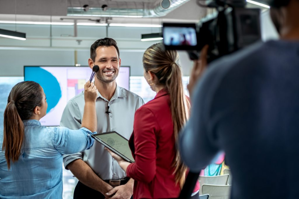 Dueño de negocio siendo filmado en anuncio de televisión. Concepto: Cómo anunciar tu negocio en televisión
