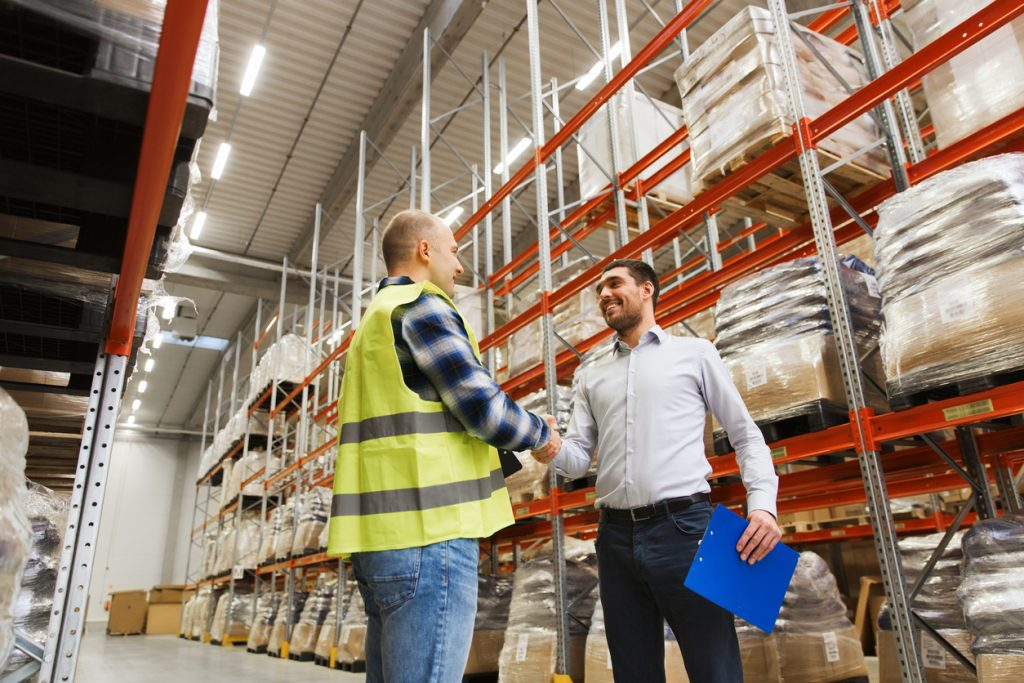 wholesale, logistic, people and export concept - manual worker and businessmen with clipboard shaking hands and making deal at warehouse. concept: corp to corp, c2c