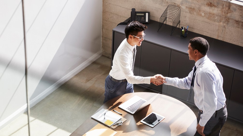Two businessmen stand shaking hands in office, elevated view. Concept: corp to corp, c2c