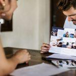 Dueño de negocio mostrando folletos de su empresa. Concepto: Cómo usar la publicidad impresa para anunciar tu negocio