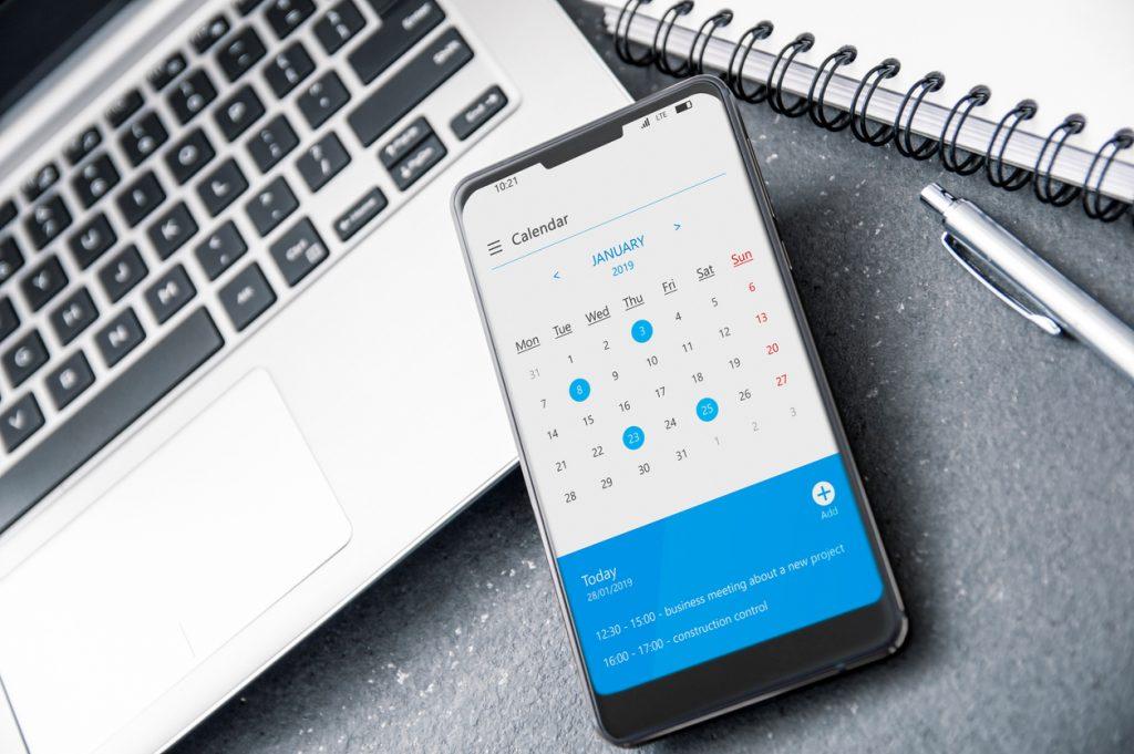 Smartphone con un calendario, app de calendario, para el año 2019 encima de una laptop. Concept: apps para negocios