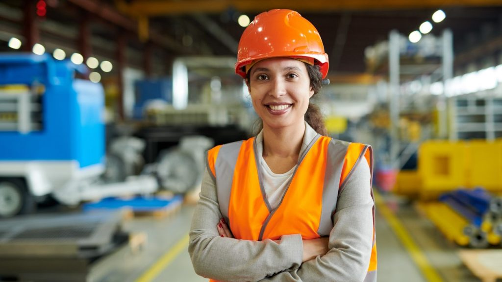 Waist up portrait of cheerful young woman wearing hardhat smiling happily looking at camera while posing confidently in production workshop, copy space. concept: networking events