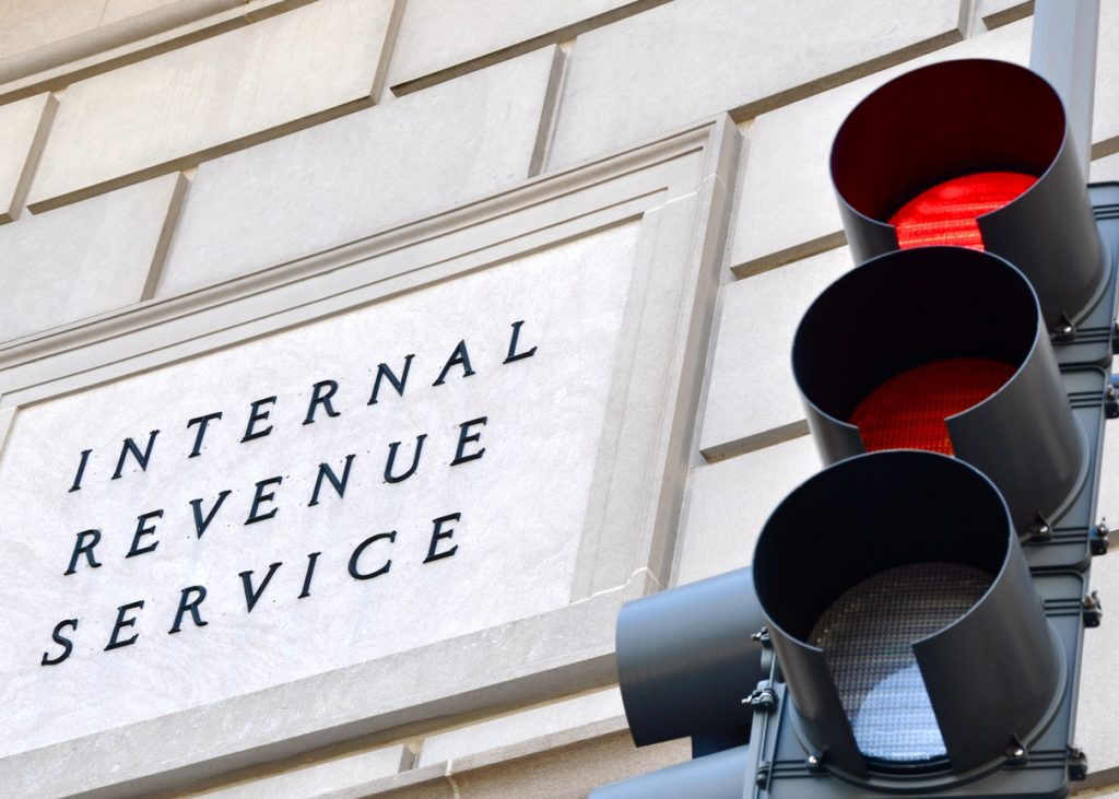 Internal Revenue Service sign with a traffic signal in the foreground indicating a red light. concept: back taxes