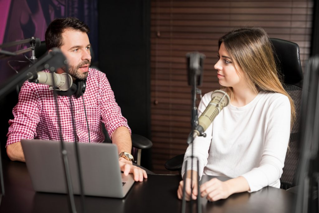 Portrait of male radio presenter interviewing a woman guest in a radio studio for a podcast. Concept: how to advertise your business on the radio.