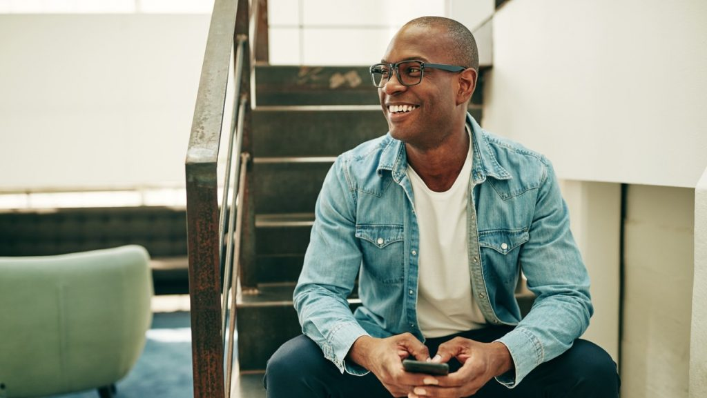 Smiling young African businessman wearing glasses and reading text messages on a cellphone while sitting on stairs in an office. concept: loan broker