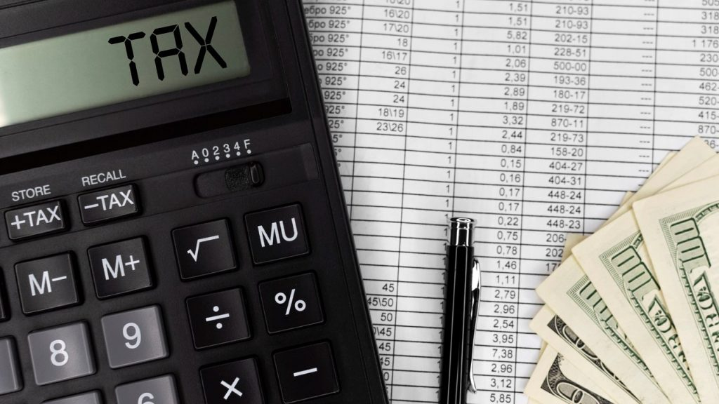 Calculator with text Tax. Calculator, currency, bills and pen. Business, finance conceptual. top view. concept: schedule k1