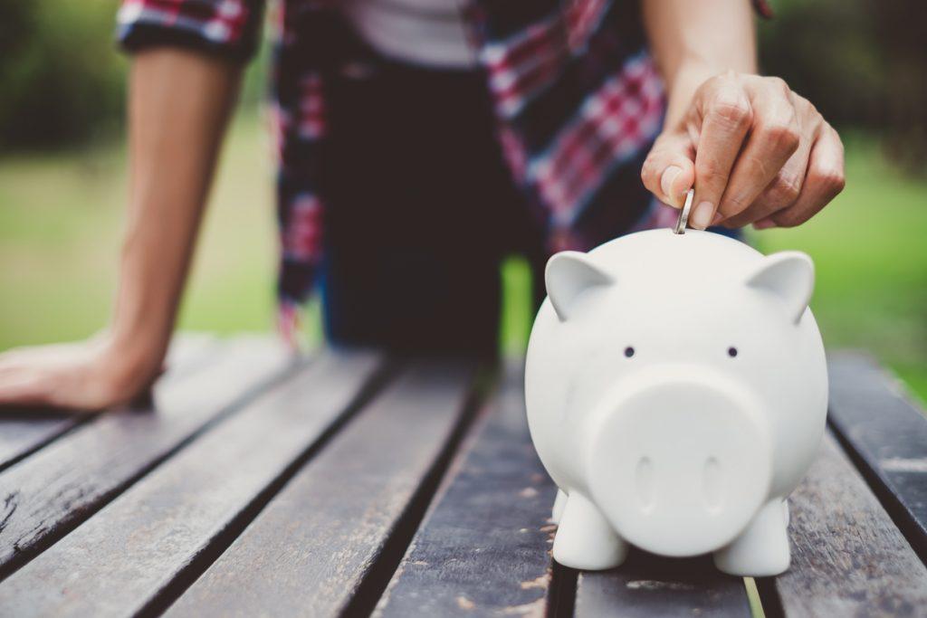 Mano poniendo dinero en alcancía, ahorros. Concept: cuentas de inversión