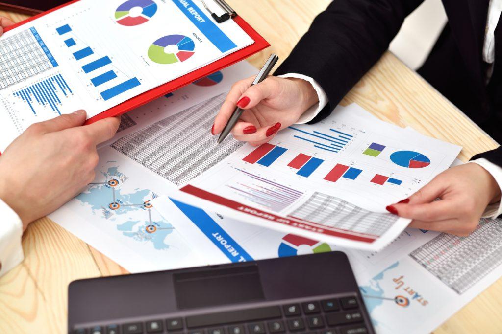 manos de mujer y de hombre sobre escritorio con papeleo, realizando un análisis de flujo de efectivo