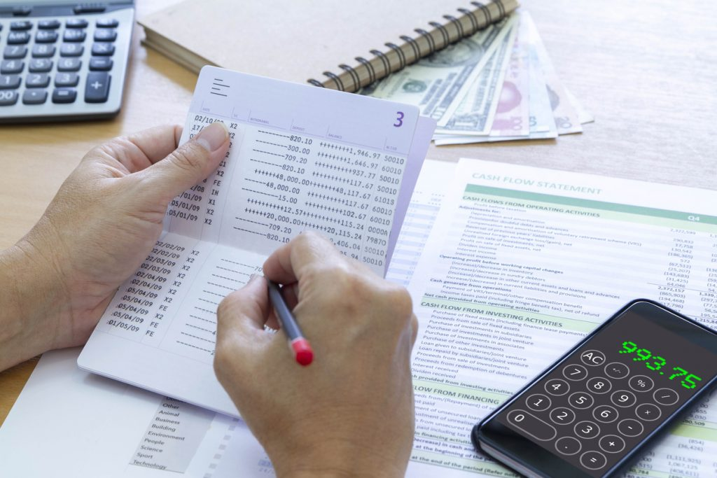 Reviewing bank passbook saving account balance and cash flow statement analysis for a return on investment, ROI, and business performance. concept: reconcile in quickbooks