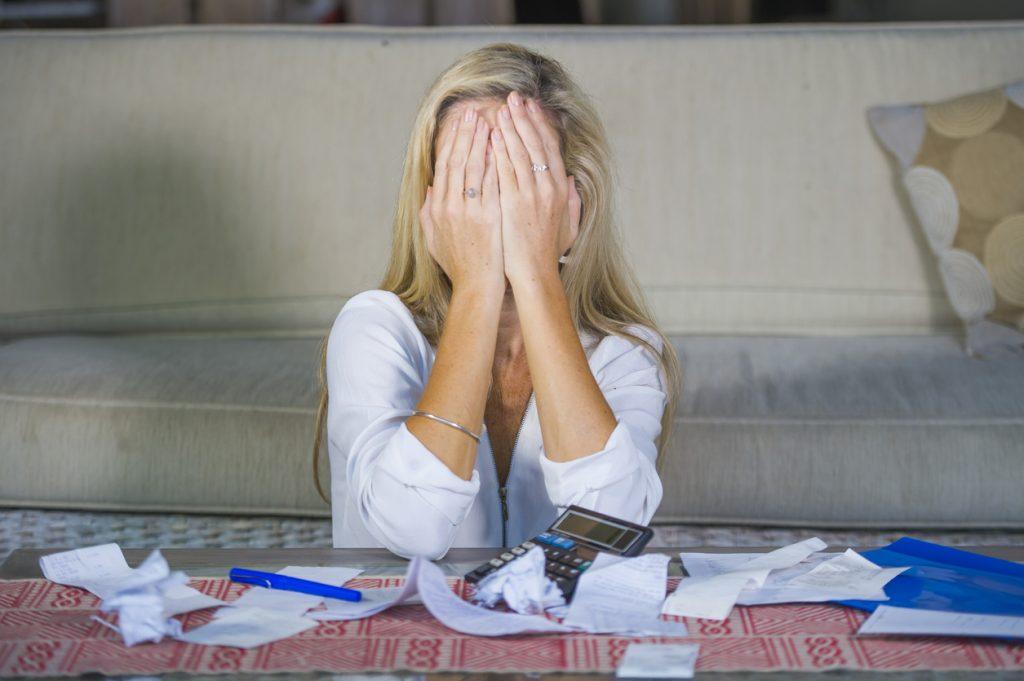 Mujer preocupada rodeada de múltiples facturas y necesitando una compañía de liquidación de deudas
