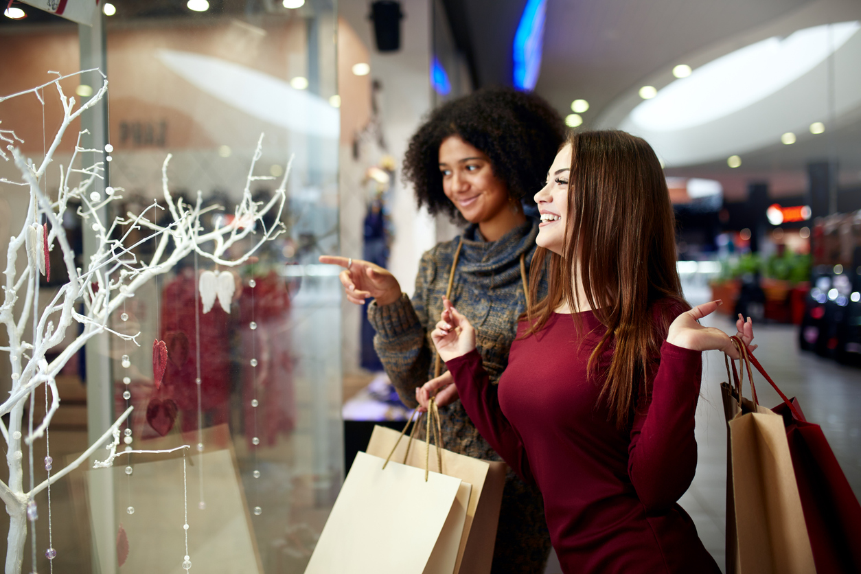 Young multiethnic diverse race women with paper shopping bags near decorated shopwindow. Girl pointing by finger at shopfront, clothes and products in mall on christmas new year sale. Black friday. concept: business hours