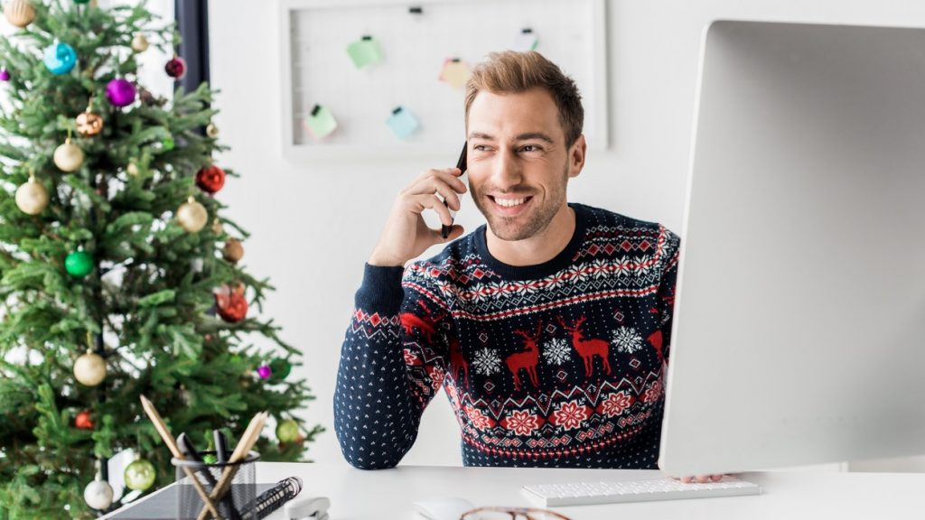 businessman in christmas sweater talking on smartphone in modern office. concept: business hours