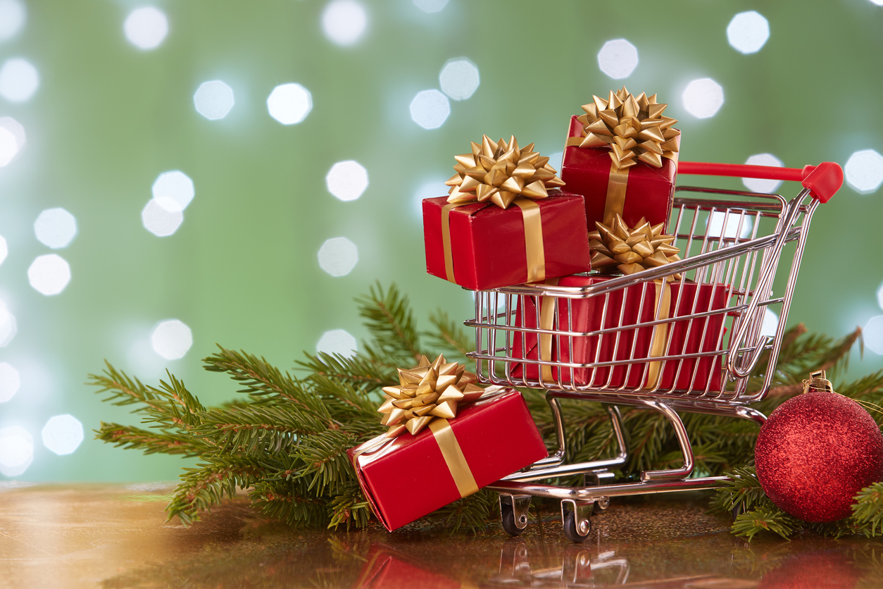 Shopping trolley with gift boxes and brenches of fir-tree with decoration on a green background with light of garland. Christmas and New Year sale. concept: marketing ideas